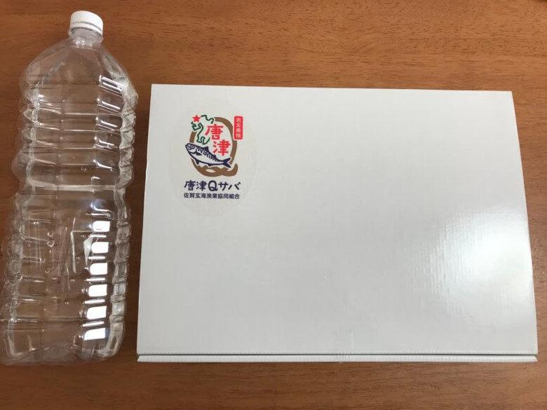 唐津Qサバのパッケージをペットボトルでくらべている写真
